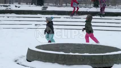 children running happy in snow storm, winter blizzard - kids playing in Washington Square Park slow motion 4K