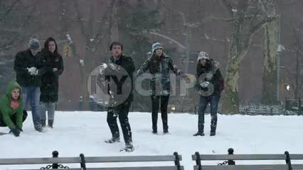 man throwing snowball over benches in winter blizzard snow storm in Washington Square Park slow motion 4K