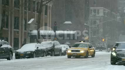 taxi cab and cars driving and man man walking bundled up in coat and hat in winter blizzard - snowing on 5th Ave in slow motion - snow in Manhattan New York City, NYC 4K and 1080 HD