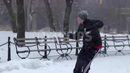 young man getting hit with snowballs in snow ball fight Washington Square Park winter blizzard - snowing in NYC