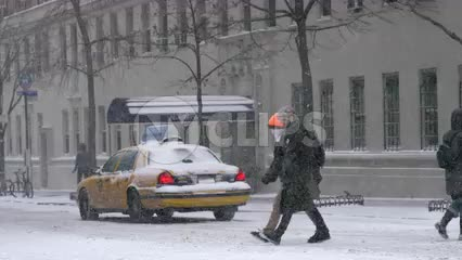 taxi cab driving in winter blizzard snow - people crossing street - snowing in Manhattan