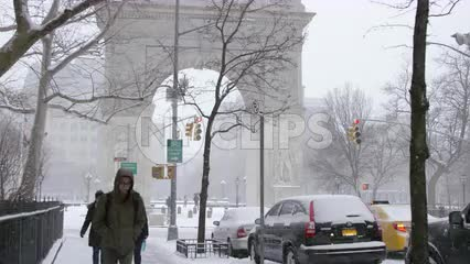 winter blizzard Washington Square Park arch snow storm people coats walking freezing cold NYC