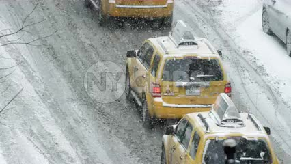 taxis in blizzard - cabs in traffic - taxicabs in winter snow storm street driving NYC
