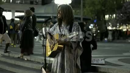 man singing and playing guitar in Union Square Park at night summer