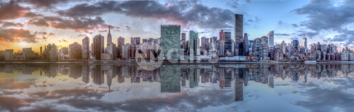 wide panoramic view of Manhattan skyline across East River with reflection of skyscrapers at sunset in NYC