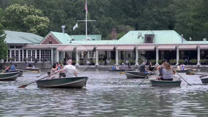 people rowing in row boats on Central Park lake, pond water in summer