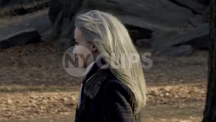 attractive woman with platinum colored hair walking in Central Park on chilly fall day in slow motion, autumn in NYC