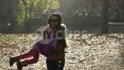 mother spinning her daughter around in circles in leafy fall meadow with changing colorful leaves on ground, slow motion Central Park 4K