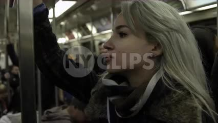 beautiful female passenger riding subway train holding on to metal pole, passengers in background, 1080 HD