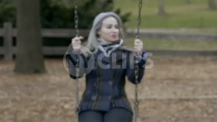 woman with coat and scarf on swing, swinging in fall autumn cold Central Park swings