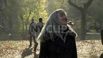 beautiful woman shaking head hair leaves in Central Park in fall autumn happy fun lady
