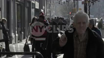 elderly man walking in midtown - cold winter day - old man carrying shopping bag over shoulder slow motion