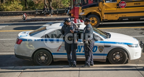 NYPD officers chatting leaning on police car on sunny Fall day in NYC