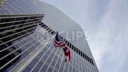 American flag waving upward angle skyscraper corporate building with sky in Midtown Manhattan New York City NYC 1080 HD