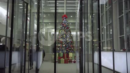 Christmas tree in corporate office building behind revolving door on holidays