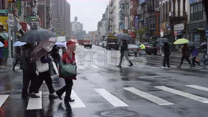 people crossing street with umbrellas on rainy day in Manhattan NYC - slow motion in 4K