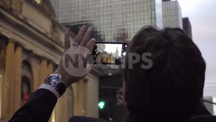 tourist man taking smartphone photo of Chrysler Building and Christmas wreath on holidays in Manhattan NYC