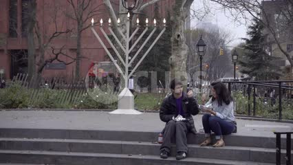 young Jewish couple picnic eating sitting by large Menorah in Washington Square Park on Chanukah in NYC