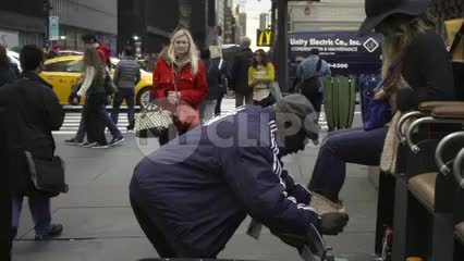 shoe shiner in Yankee jacket shining woman's boots on 42nd st and 5th avenue on crowded street during day, slow motion Manhattan NYC