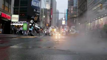 steaming manhole low view on midtown street in Manhattan on rainy day in 1080 HD