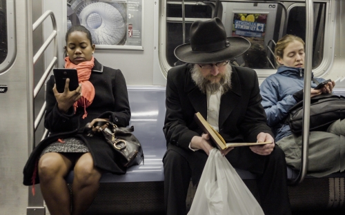 black woman and Jewish man on subway reading - diversity on public transportation in New York City NYC