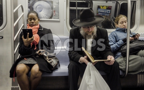 black woman and Jewish man on subway reading - diversity on public transportation in New York City NYC