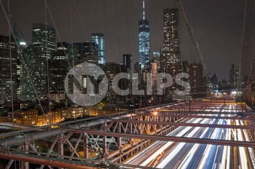 Brooklyn Bridge at night with fast cars traffic streaking lights at night Freedom Tower Manhattan buildings in background in New York City NYC