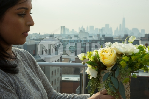 Brooklyn woman arranging flowers on rooftop with Manhattan skyline in background in New York City