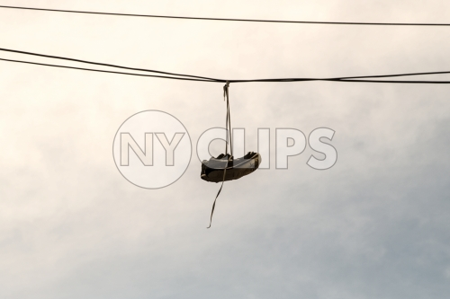shoes dangling on wire - gritty sneakers hanging on cable - shoefetty