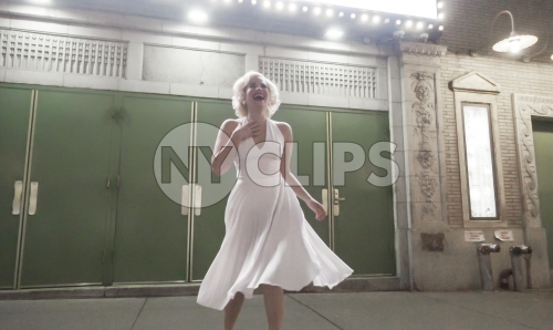 Marilyn Monroe look alike laughing in front of green Broadway theater doors in New York City NYC