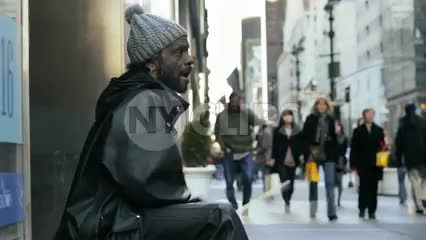 homeless man drumming on buckets, drummer in street on cold winter day Midtown Manhattan