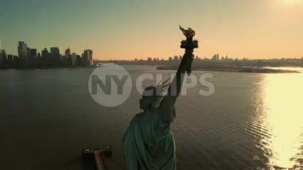 Statue of Liberty during day - aerial circling medium shot with Manhattan New York City skyline in background -n NYC 4K and 1080 HD