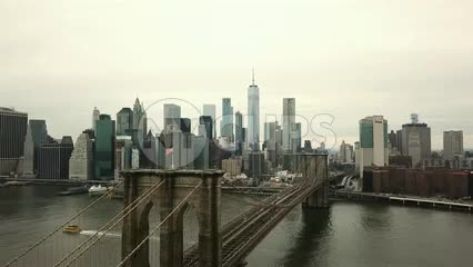 aerial flying over Brooklyn Bridge with American flag toward Manhattan skyline with Freedom Tower and skyscrapers in 4K and 1080 HD