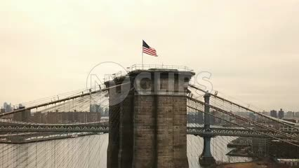 American flag on Brooklyn Bridge waving - aerial circling toward Brooklyn side of Bridge in NYC 1080 HD