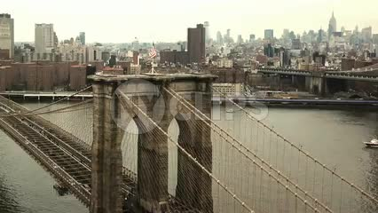 aerial flying over American flag on Brooklyn Bridge straight ahead toward Manhattan buildings on East River in 1080 HD