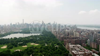 Central Park aerial moving forward toward buildings over green Manhattan New York City NYC