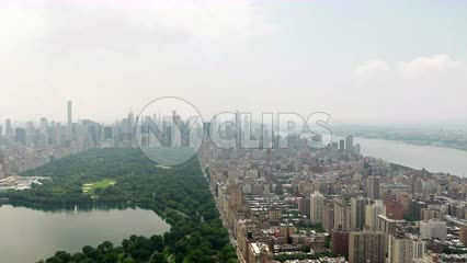 Central Park aerial pulling backwards from buildings over green trees New York City NYC