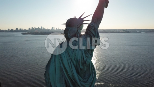 Statue of Liberty back in New York Harbor - aerial over water in NYC