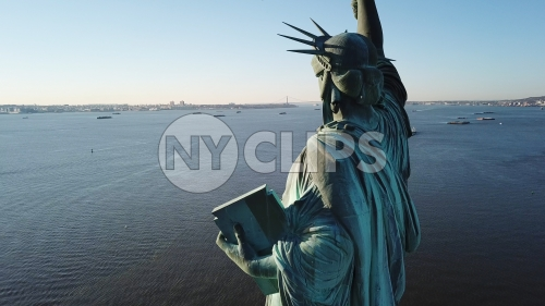 Statue of Liberty facing open harbor in New York City - aerial in water
