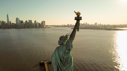 Statue of Liberty at golden sunset with Manhattan skyline in background - aerial on New York Harbor in NYC