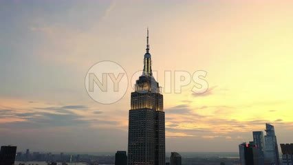 aerial circling Empire State Building at sunset colorful clouds in sky over famous skyscraper New York City NYC