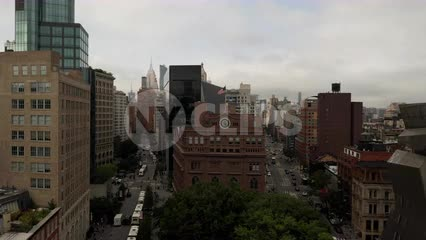 aerial flying over American flag and clock on Cooper Union building with cityscape above in Manhattan New York City NYC
