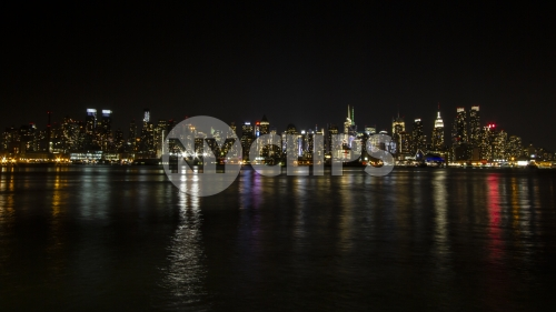 Manhattan skyline at night with reflections off water New York City NYC