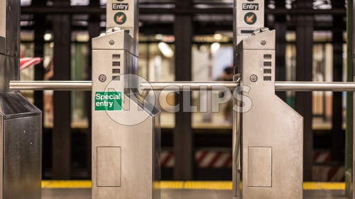 subway turnstile in station with special entry sign - empty platform in New York City NYC