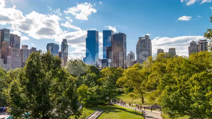 Manhattan Skyscrapers over Central Park trees on bright sunny day in timelapse in 4K and 1080 HD in NYC