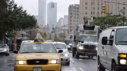 taxi cab driving in rain on wet road - 6th Ave with Freedom Tower in background in Manhattan NYC