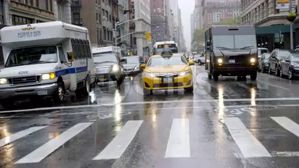 taxi cab driving past crosswalk on wet road in rain with windshield wipers - 4K slow motion in Manhattan NYC