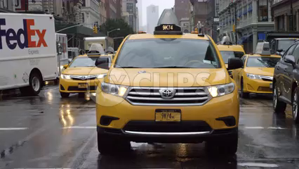 taxicabs driving in rain - raining on taxi in traffic during day - Manhattan NYC