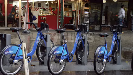 CitiBikes parked at docking station on street - 4K slow motion tracking of blue bicycles