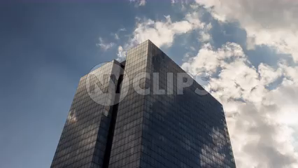 towering glass skyscraper in Manhattan with American flag - 4K timelapse in New York City